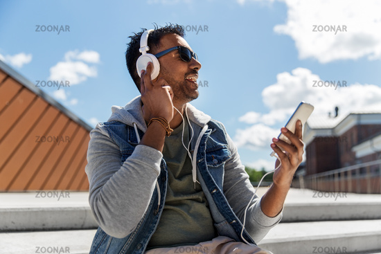 man with smartphone and headphones on roof top