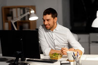 businessman at computer eating at night office