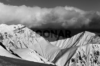 Black and white sunny snowy mountains in evening