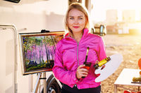 Pretty painter middle aged blond woman holds paint brush