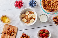 Healthy breakfast ingredients with homemade granola and berries on white wooden background