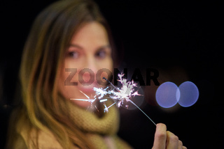 Beautiful woman having fun, with sparkler in her hands celebrating new year eve