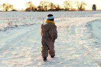 Little toddler walking outdoors in a snowy winter scene.