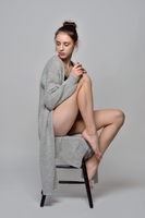 beautiful barefoot woman in cardigan on the chair