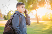 Young Hispanic Boy Walking Outdoors With Backpack Talking on Cell Phone