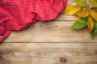 Red Tablecloth And Autumn Leaves On Wooden Background