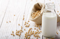 Non-dairy alternative Soy milk or yogurt in glass bottle on white wooden table with soybeans in hemp sack