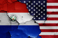 flags of Paraguay and USA painted on cracked wall