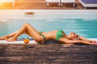 Beautiful blonde girl in good shape and tan skin lying near the pool beach.