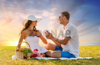 smiling couple with small red gift box at picnic