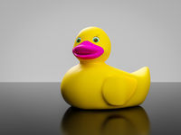 yellow rubber duck with pink mouth and green eyes