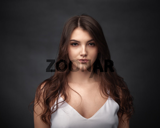 Dramatic portrait of a beautiful girl on a dark background