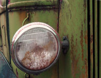 close up of the headlight of an old abandoned truck with rusted green grille and panels