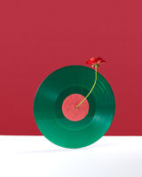 Composition of a red flower decorating a vinyl audio record on a double white red background with copy space