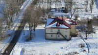rural house with red roof in the snow