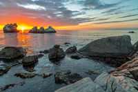 Sunset over sea and stone shore