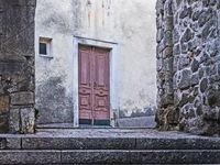 Altes Gebäude mit roter Tür in der Altstadt der Stadt Rab auf der Insel Rab, Kroatien