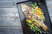 Traditional BBQ parrotfish with mango salsa as top view on a black board with copy space left
