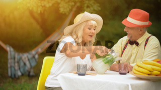 The Old Couple Is Drinking Cold Lemonade In The Summer Garden