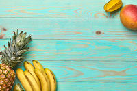 Mango, carambola, banana, pineapple on a blue wooden background with copy space. Tropical Fruits. Flat lay