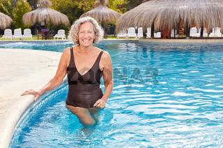 Glückliche Senior Frau steht im Pool