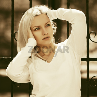 Young fashion blond woman in white pullover