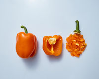 Organic yellow paprika peppers with slice and half isolated on gray