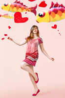 Young woman portrait with flying kites over pink background