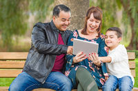 Caucasian Mother and Hispanic Father Using Computer Tablet With Mixed Race Son Outdoors