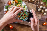 Hands of a girl with a phone make a photo of a freshly prepared salad. Food blogging concept. Top view