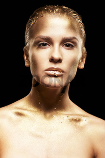 Female with unusual metal face makeup. Golden girl on black background