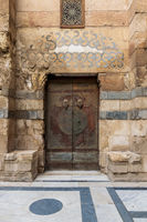 Wooden decorated copper plated door and stone bricks wall, Old Cairo, Egypt