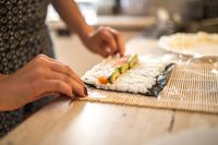 A Woman preparing homemade sushi and rolls. Forming sushi. The steps for creating sushi. View of process of preparing rolling sushi.