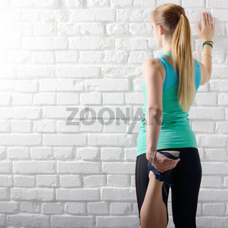 Young caucasian woman doing stretching exercises for legs near white brick wall. Healthy lifestyle.