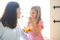 Little girl with her mother in the kitchen eating a fresh fruit salad