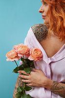 Attractive female with tattoo on her shoulders and hands holds bouquet of coral roses on a blue background, place for text. A gift for Mother's Day.