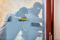 Einbrecher beim Aufbrechen einer Tür mit Brechstange