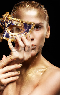 Golden girl on black background. Female with masquerade venecian, mask in hand near face.