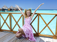 Young beautiful girl stands in pink sundress on sundeck of villa on water