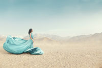 Portrait of beautiful young woman in long fluttering dress posing outdoor at sandy desert
