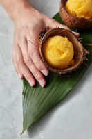 A mango ice cream sorbet in a coconut shell is held by a female hand on a palm leaf on a gray concrete background. Top view
