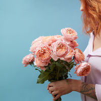 Gentle pink roses in the hands of a girl with a tattoo on a blue background with copy space for text. Birthday present