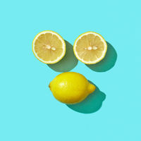 Two halves and a whole ripe lemon in the shape of a face with shadow reflection on a blue background and copy space. Flat lay