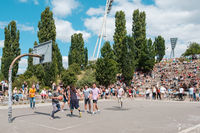 Boys and girls playing basketball in park (Mauerpark) next to crowd of people in amphitheater watching performance on a sunny summer sunday in Berlin