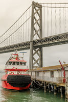 San Francisco Fireboat moored with the Bay Bridge in the background.