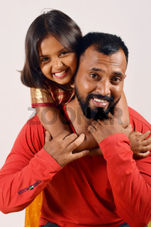 Little girl hugging her father and on his shoulders. Pune, Maharashtra