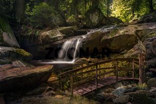Wasserfall neben einem Steg im Wald