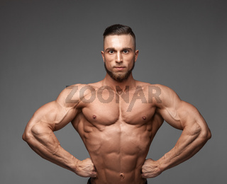 muscular super-high level handsome man posing on gray background
