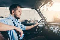 Handsome man sitting inside his old vintage car
