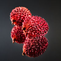 Tropical ripe litchi fruit isolated on a black glossy background